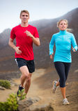 Fitness sport couple running jogging outside on trail. Fitness sport couple jogging outside, training together outdoors. Running on nature trail Royalty Free Stock Photo