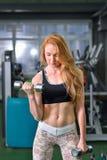 Fitness, sport, die levensstijl uitoefenen - Aantrekkelijke jonge vrouw die gewichtheffenoefeningen doen bij gymnastiek stock fotografie