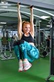 Fitness, sport, die levensstijl uitoefenen - Geschikte vrouw die oefeningen op rekstok in gymnastiek doen Royalty-vrije Stock Foto