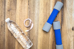 Fitness and sport equipment. Measuring tape,bottle of water and dumbells Stock Photography