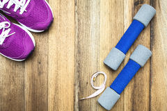 Fitness and sport equipment. Measuring tape,mat,sneakers,towel,bottle of water with wooden background on top view Stock Photos