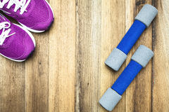 Fitness and sport equipment. Measuring tape,mat,sneakers,towel,bottle of water with wooden background on top view Royalty Free Stock Images