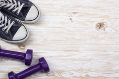 Fitness and sport equipment :sneakers, dumbbells on wooden background Stock Images
