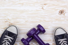 Fitness and sport equipment :sneakers, dumbbells on wooden background Royalty Free Stock Images