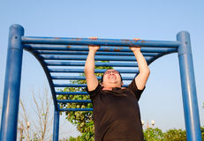 Fitness ,sport, exercise, training and lifestyle concept. One young adult fat man doing pull ups on horizontal bar outdoors for losing weight in evening Stock Photo