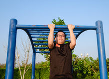 Fitness ,sport, exercise, training and lifestyle concept. One young adult fat man doing pull ups on horizontal bar outdoors for losing weight in evening Royalty Free Stock Photo