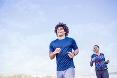 fitness, sport, exercising and healthy lifestyle concept - couple running or jogging. stock photography