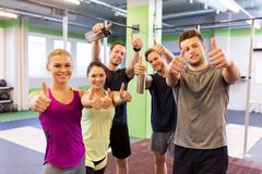 Group of happy friends in gym showing thumbs up Royalty Free Stock Photo