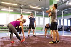 Group of happy friends stretching in gym Royalty Free Stock Image