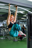 Fitness, sport, exercising lifestyle - Fit woman doing exercises on horizontal bar in gym stock images
