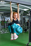 Fitness, sport, exercising lifestyle - Fit woman doing exercises on horizontal bar in gym royalty free stock photo
