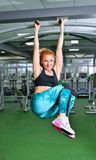 Fitness, sport, exercising lifestyle - Fit woman doing exercises on horizontal bar in gym stock photo