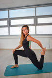 Fitness, sport, exercising lifestyle - Fit woman doing stretching exercises in a gym royalty free stock images