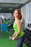 Fitness, sport, exercising lifestyle - middle age woman doing exercises with dumbbell at gym on broadest muscle of back Stock Photo