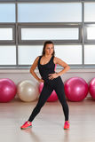 Fitness, sport, exercising lifestyle - middle aged woman in bodysuit posing at gym stock photo