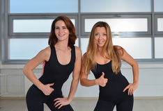 Fitness, sport, exercising lifestyle - Two happy young women standing close together in a gym and showing thumbs up Stock Photography