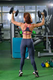 Fitness, sport, exercising lifestyle - woman with dumbbells doing exercises in gym, view from back Stock Photos