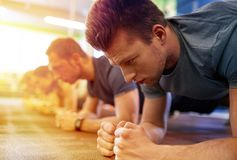 Man doing plank exercise at group training in gym. Fitness, sport, exercising and people concept - close up of men doing plank exercise at group training in gym stock images