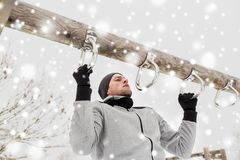 Young man exercising on horizontal bar in winter. Fitness, sport, exercising, training and people concept - young man doing pull ups on horizontal bar outdoors Stock Photo