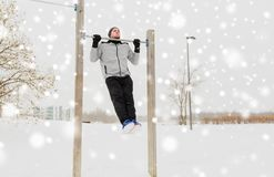Young man exercising on horizontal bar in winter. Fitness, sport, exercising, training and people concept - young man doing pull ups on horizontal bar outdoors Royalty Free Stock Photo
