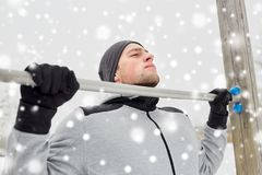 Young man exercising on horizontal bar in winter. Fitness, sport, exercising, training and people concept - young man doing pull ups on horizontal bar outdoors Royalty Free Stock Photos