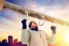 Young man exercising on horizontal bar in winter. Fitness, sport, exercising, training and people concept - young man doing pull ups on horizontal bar outdoors Royalty Free Stock Images