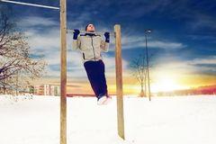 Young man exercising on horizontal bar in winter. Fitness, sport, exercising, training and people concept - young man doing pull ups on horizontal bar outdoors Royalty Free Stock Photography