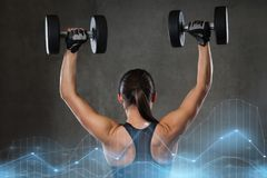 Young woman flexing muscles with dumbbells in gym Royalty Free Stock Images