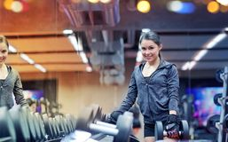 Smiling young woman choosing dumbbells in gym Stock Image