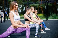 Fitness, sport, friendship and healthy lifestyle concept - group of attractive young women doing lunge outdoors. Stock Images