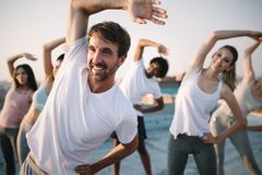 Fitness, sport, friendship and healthy lifestyle concept . Group of happy people exercising stock image