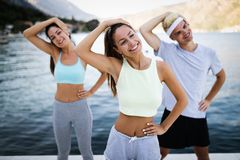 Group of happy friends or sportsmen exercising and stretching outdoor. Fitness, sport, friendship and healthy lifestyle concept. Group of happy friends or royalty free stock photos