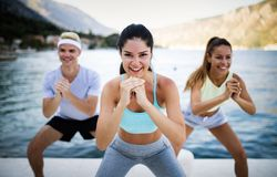 Group of happy friends or sportsmen exercising and stretching outdoor. Fitness, sport, friendship and healthy lifestyle concept. Group of happy friends or stock photos