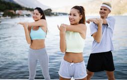 Group of happy friends or sportsmen exercising and stretching outdoor. Fitness, sport, friendship and healthy lifestyle concept. Group of happy friends or royalty free stock image