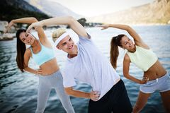 Group of happy friends or sportsmen exercising and stretching outdoor. Fitness, sport, friendship and healthy lifestyle concept. Group of happy friends or stock image