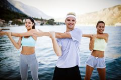 Group of happy friends or sportsmen exercising and stretching outdoor. Fitness, sport, friendship and healthy lifestyle concept. Group of happy friends or royalty free stock photography