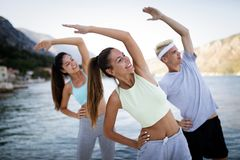 Group of happy friends or sportsmen exercising and stretching outdoor. Fitness, sport, friendship and healthy lifestyle concept. Group of happy friends or stock photography