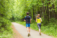 Fitness, sport, friendship and lifestyle concept - smiling couple running outdoors. Royalty Free Stock Photos