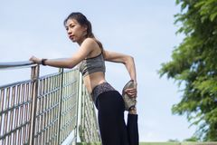 Fitness sport girl fashion sportswear doing yoga fitness exercise in street. Fit young asian woman doing training workout. Royalty Free Stock Photos