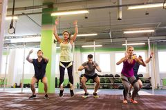Group of people exercising and jumping in gym. Fitness, sport and healthy lifestyle concept - group of people exercising and jumping in gym Stock Photo