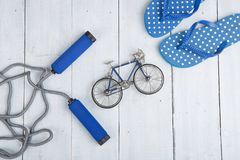 Fitness/sport and healthy lifestyle concept - Jumping/skipping rope with blue handles, flip flops in polka dots and model of. Bicycle on white wooden background stock images