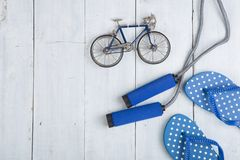 Fitness/sport and healthy lifestyle concept - Jumping/skipping rope with blue handles, flip flops in polka dots and model of. Bicycle on white wooden background stock photos