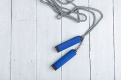 Fitness/sport and healthy lifestyle concept - Jumping/skipping rope with blue handles. On white wooden background, equipment, exercise, gym, object, training stock photo