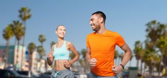 Smiling couple jogging at summer over venice beach Stock Photo