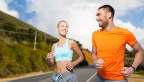 Smiling couple running over big sur hills stock photography