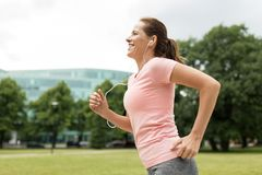 Woman with earphones running at park. Fitness, sport and healthy lifestyle concept - smiling woman with earphones running at park and listening to music Stock Image