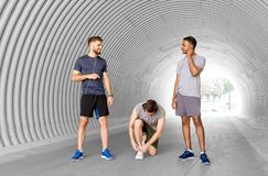 Male friends with earphones training outdoors
