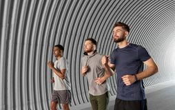 Young men or male friends running outdoors