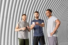 Sporty men or friends with smartphone outdoors