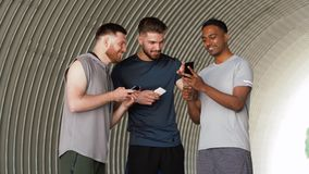 Sporty men or friends with smartphones outdoors